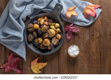 Roasted chestnuts with salt in cast iron grilling pan over rustic wooden board. Top view. Flat lay.