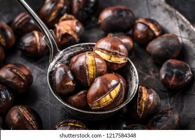Roasted chestnuts served in chestnut pan on an old table