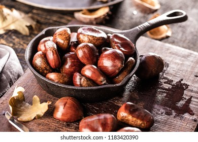 Roasted chestnuts served in a special perforated chestnut pan on an old wooden table