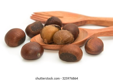 roasted chestnuts in wooden spoon on white background