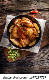Roasted chicken and american potatoes with chili peppers and herbs - Top of view.