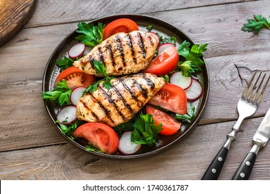 Roasted chicken breast, fillet, steak and fresh vegetable salad close up. Healthy keto, ketogenic lunch menu with grilled chicken meat and organic veggies and greens.