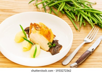 Roasted chicken breast with mashed potatoes or puree, French beans or green beans and mushroom sauce in a white plate aside a fork, a folding knife and a pile of natural green beans on a wood table.