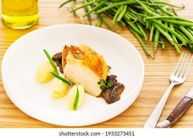 Roasted chicken breast with mashed potatoes or puree, French beans and mushroom sauce in a white plate aside a fork, a knife, a bottle of oil and a pile of natural green beans on an oak wood table.