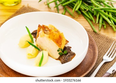 Roasted chicken breast with mashed potatoes, French beans and mushroom sauce in a plate aside a fork, a folding knife, a bottle of olive oil and a pile of raw green beans on a jute mat on an oak table