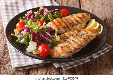 roasted Chicken breast with mix salad of chicory, tomatoes and lettuce on a plate close-up. Horizontal