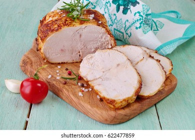 Roasted chicken breast for sandwiches on a wooden cutting board on a blue wooden background. Easy food. Healthy eating concept