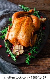 Roasted chicken with cranberries, rosemary and garlic  on wooden table, top view.