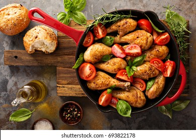 Roasted chicken drumsticks in a cast iron pan with tomatoes and basil