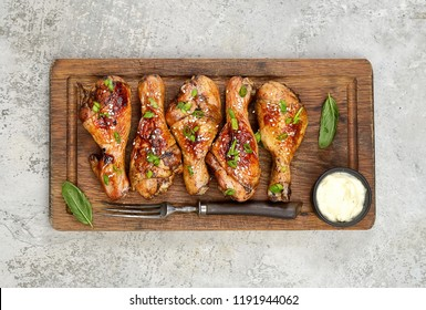 Roasted chicken drumsticks with sesame  on slate on gray  background