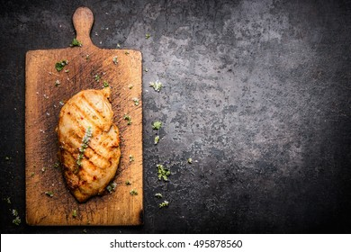Roasted Chicken fillet on aged wooden cutting board and dark vintage background, border, place for text