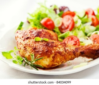Roasted chicken leg with cherry tomatoes, cucumber, leek, lettuce and fresh herbs. Concept for a tasty and healthy meal. Homemade food. White background. Close up.