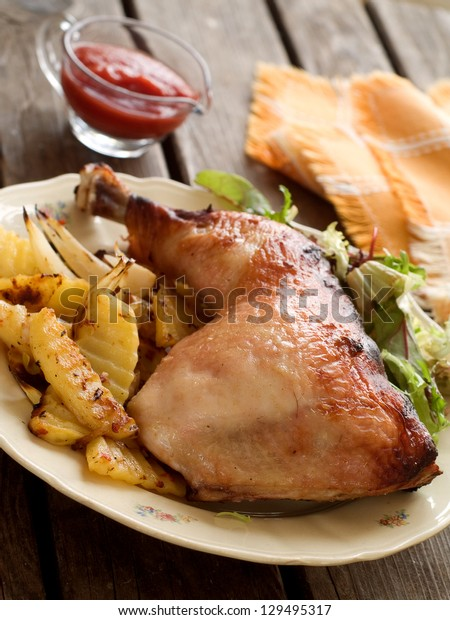 Roasted chicken leg with fried potato and salad, selective focus