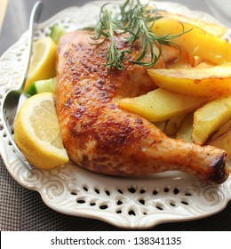 roasted chicken leg with fries potato and lemon