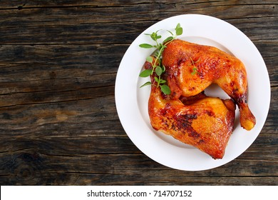 roasted chicken leg quarters with crispy golden brown skin with fresh green thyme leaves on white plate on dark wooden boards, view from above