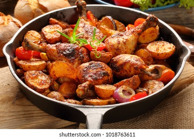 Roasted chicken legs with baked potato on frying pan