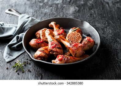Roasted chicken legs in cast iron skillet, selective focus