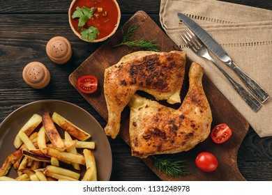 Roasted chicken legs with fried potatoes and tomato dip.