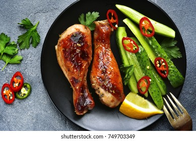 Roasted chicken legs garnished with fresh cucumbers on a black plate over dark grey slate,stone or concrete background.Top view.