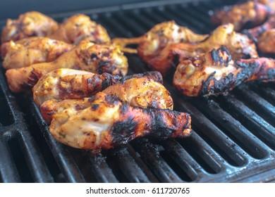 Roasted chicken legs. Grilled chicken legs on black grill. Chicken in garlic marinade in flames.