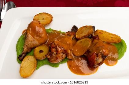Des cuisses de poulet rôties avec des pommes de terre rôties et de la purée de pois prête à manger