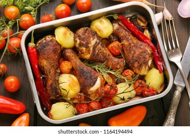 Roasted chicken legs with potatoes and vegetables on the pan