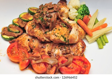 Roasted chicken with mushroom sauce on white dish