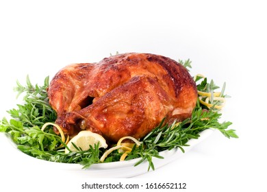 Roasted chicken on plate of fresh herbs with lemon garnish, white background