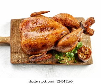 roasted chicken on wooden cutting board, top view