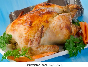 Roasted chicken on wooden table. Selective focus
