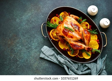 Roasted chicken with oranges ,rosemary and cranberries in a skillet pan.Top view with copy space.