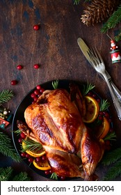 Roasted chicken with oranges ,rosemary and cranberries on a christmas table. Top view with copy space.