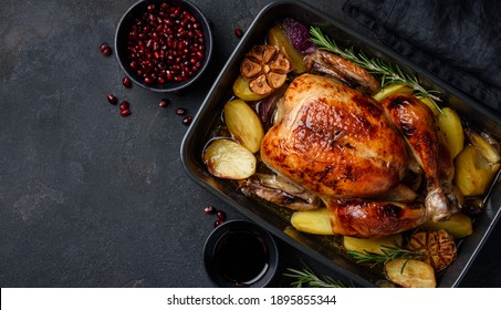 Roasted chicken in pomegranate sauce with potatoes in a gray ceramic mold. Dark background. Top view. Copy space
