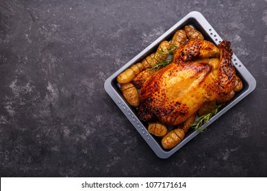 Roasted chicken and potatoes on black slate stone background, flat lay with copy space. Menu or recipe template