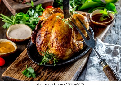 Roasted chicken with rosemary served on black plate with sauces on wooden table, close up.