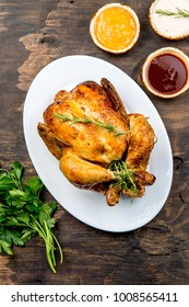 Roasted chicken with rosemary srved with sauces on wooden table, top view