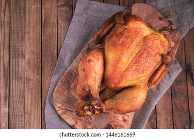 Roasted chicken served with sauces on wooden table.
