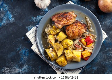 Roasted chicken thighs with potatoes on a plate