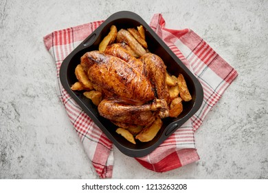 Roasted chicken or turkey with potatoes in black steel mold placed on napkin, flat lay with copy space on stone background. Top view.