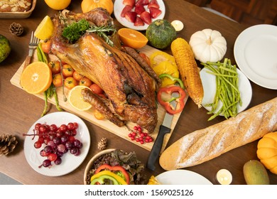 Roasted  chicken or turkey with sauce and grilled autumn vegetables: corn,pumpkin  on wooden table, top view, frame. Christmas or Thanksgiving Day food concept.