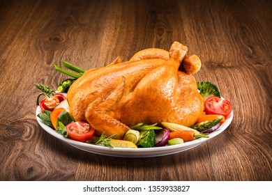 Roasted chicken with vegetables on a wooden table