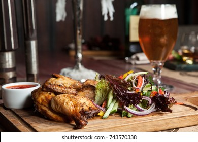 roasted chicken with vegetables on a wooden Board. next to a glass of light beer. in the restaurant, Traditional cuisine