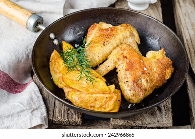 Roasted chicken wings with fried potatoes in iron pot on wooden background