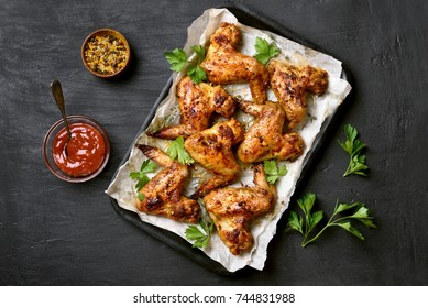 Roasted chicken wings on baking tray over black stone background, top view.