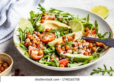 Roasted chickpea salad with avocado and tomatoes in a white bowl. Healthy vegan food concept.