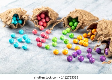 Roasted chickpeas covered in chocolate, fruit sauce. colorful candies, chocolate roasted chickpeas. Colorful starchy roasted chickpea in a linen sack.