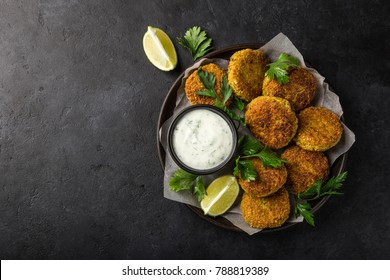 roasted chickpeas falafel patties with garlic yogurt sauce. Top view. black background