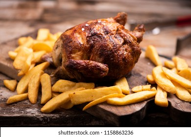 roasted chiken on wooden board with chips