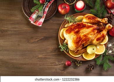 Roasted Christmas Chicken or Turkey for Christmas Dinner. Festive decorated wooden table for Christmas Dinner with baked stuffed chicken, copy space.