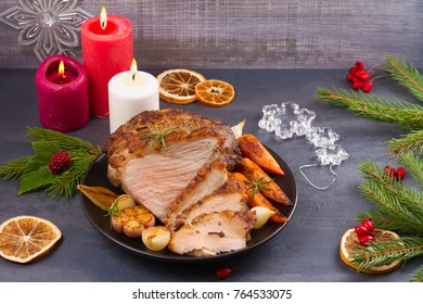 Roasted Christmas ham on black plate and festive decoration. Dinner for Christmas and New Year evening